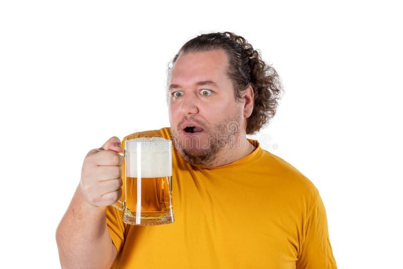 Gros homme drôle se sentant heureux et décontracté, tenant la bière froide fraîche dans des ses mains sur le fond blanc images libres de droits
