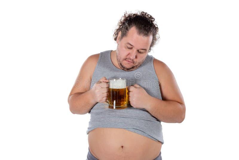 Gros homme drôle se sentant heureux et décontracté, tenant la bière froide fraîche dans des ses mains sur le fond blanc photo stock