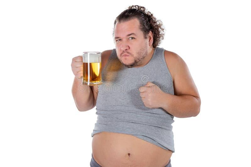 Gros homme drôle se sentant heureux et décontracté, tenant la bière froide fraîche dans des ses mains sur le fond blanc photo libre de droits