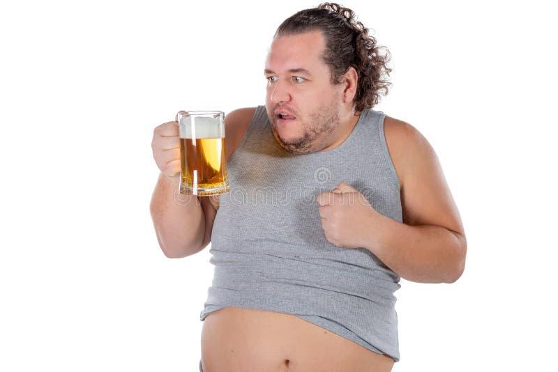 Gros homme drôle se sentant heureux et décontracté, tenant la bière froide fraîche dans des ses mains sur le fond blanc image libre de droits