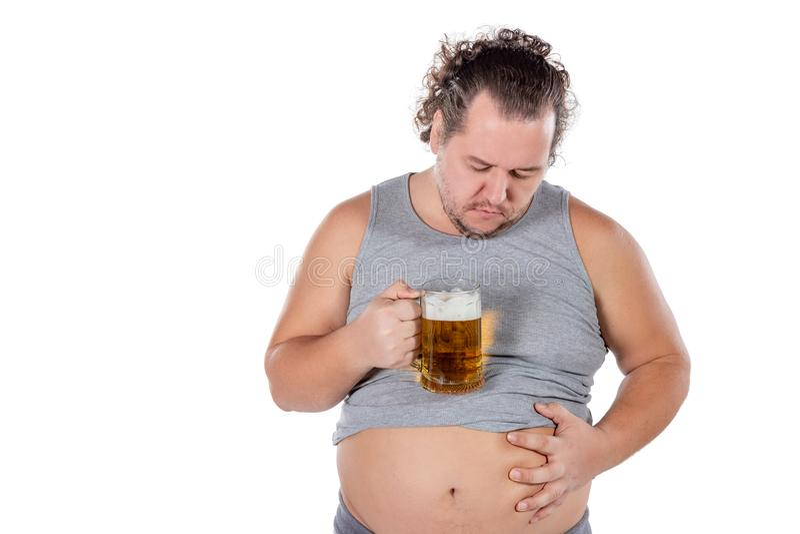 Gros homme drôle se sentant heureux et décontracté, tenant la bière froide fraîche dans des ses mains sur le fond blanc image stock