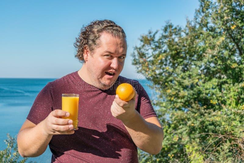 Gros homme drôle sur les fruits potables de jus et de consommation d'océan Vacances, perte de poids et consommation saine photos libres de droits