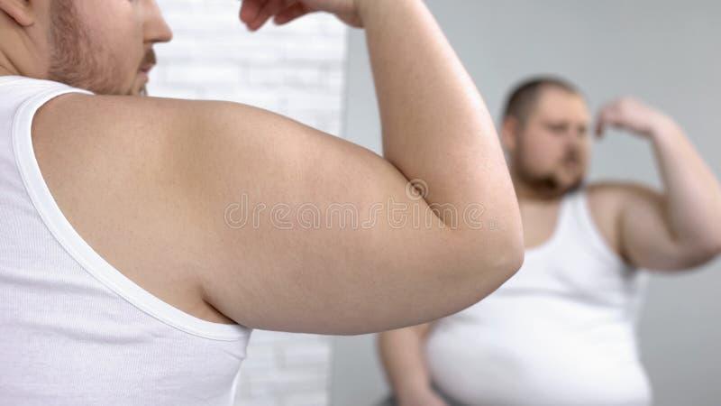 Gros mâle regardant ses muscles faibles de bras, peau de fléchissement, rêvant du biceps photos stock