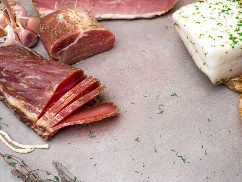 Gros morceaux de fond salé de saindoux, épices et herbes, jambon fumé vitré fait maison et viande saccadée avec les herbes nature images stock