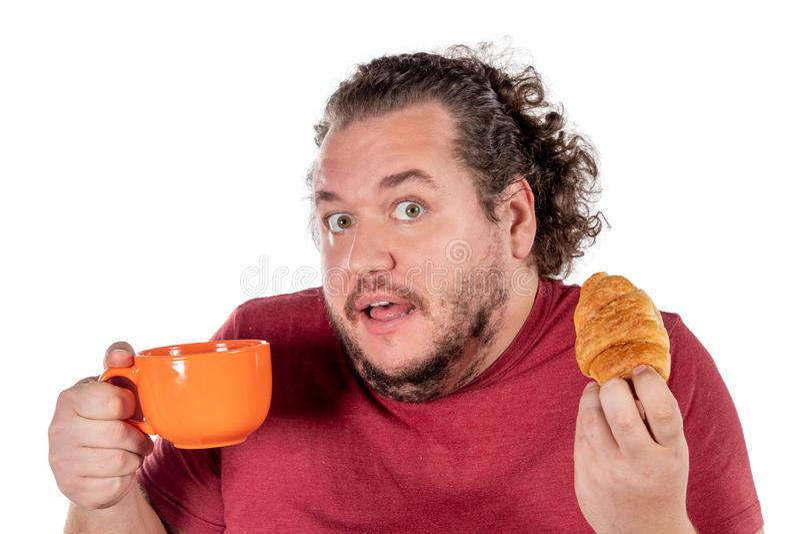 Gros petit croissant mangeur d'hommes drôle et café potable de grande tasse orange sur le fond blanc Bonjour et petit déjeuner photo libre de droits
