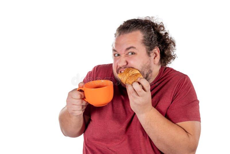 Gros petit croissant mangeur d'hommes drôle et café potable de grande tasse orange sur le fond blanc Bonjour et petit déjeuner image libre de droits