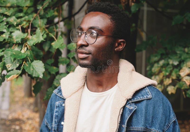 Gros plan d'un Africain moderne pensant et regardant loin en portant des lunettes dans le parc de la ville d'automne sur fond images libres de droits