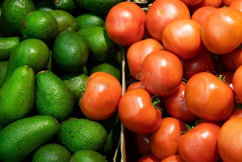 Gros plan de tomates rouges fondantes et d'avocats verts sur le comptoir du supermarché photos libres de droits