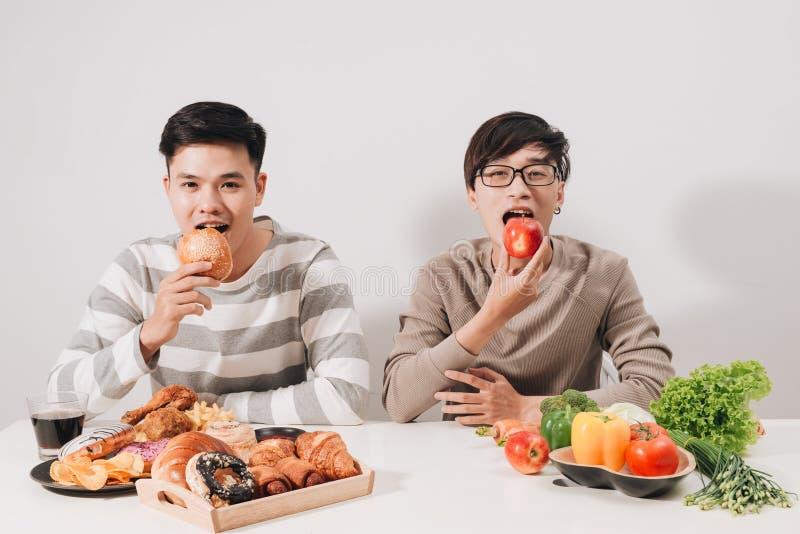 Gros renversement avec des plateaux avec la nourriture sur la table blanche Concept malsain de mode de vie Homme s'asseyant Deux  images stock