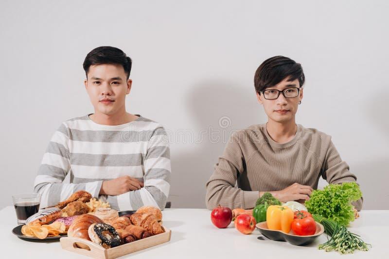 Gros renversement avec des plateaux avec la nourriture sur la table blanche Concept malsain de mode de vie Homme s'asseyant Deux  photo stock