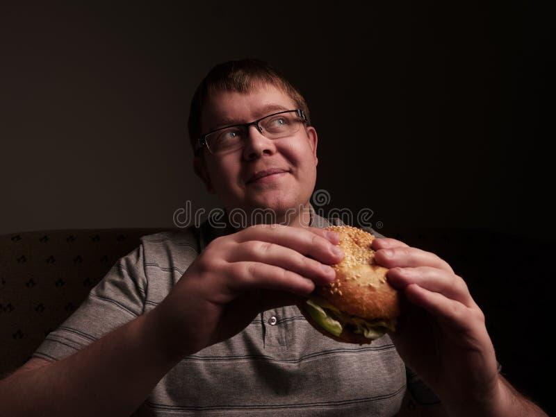 Gros type seul mangeant l'hamburger Mauvaises habitudes alimentaires images libres de droits