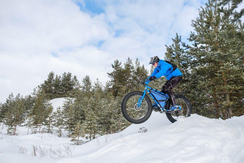 Gros vélo Gros vélo de pneu Un jeune homme montant la grosse bicyclette pendant l'hiver photo libre de droits