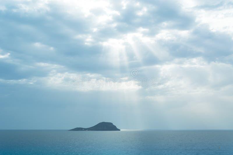 Grosa由太阳光芒的海岛剪影Iluminated通过云彩 免版税库存照片