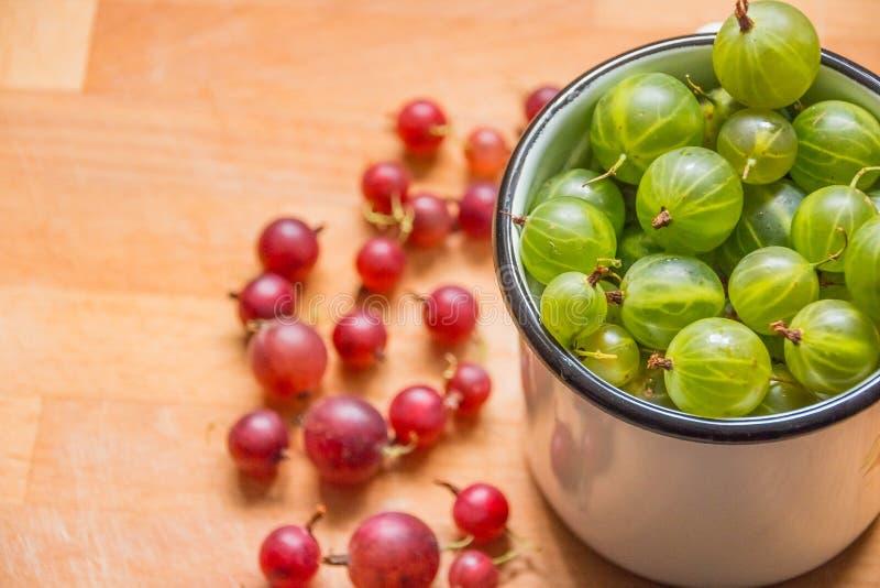 Groseilles à maquereau dans une tasse Baies fraîches de groseilles à maquereau groseille à maquereau verte rouge sur le fond en b photographie stock