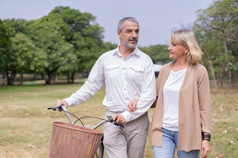 Grossältere Leute entspannen sich im Park beim Radfahren und Gesprächen am Morgen im Park Das Konzept der guten Gesundheit und En stockbilder