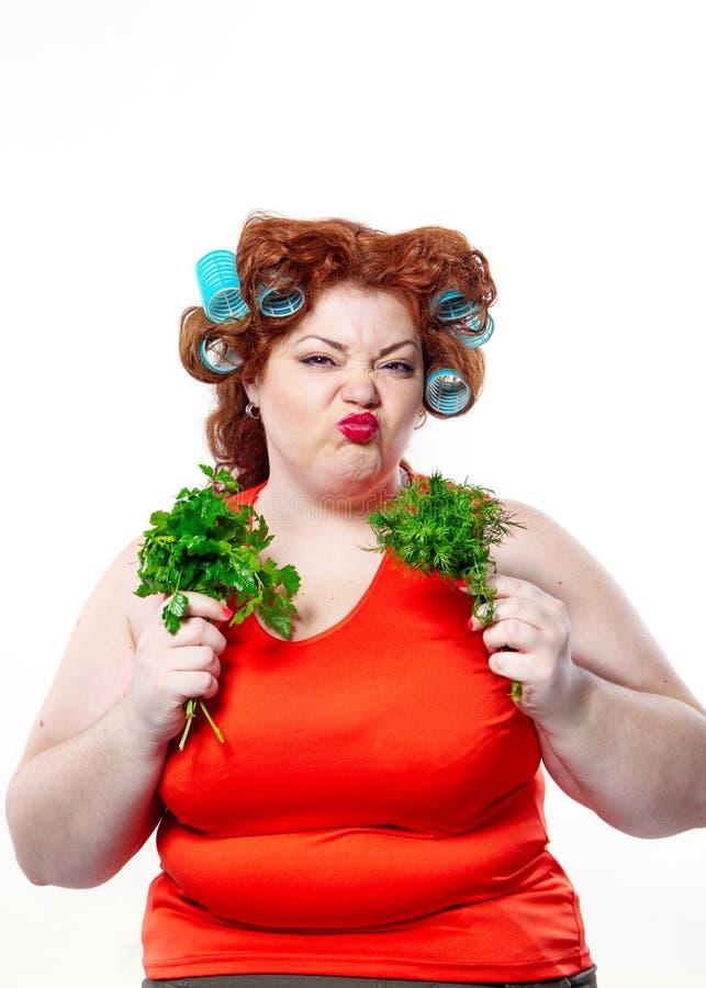 Grosse femme avec le rouge à lèvres rouge de sensualité dans des bigoudis à un régime tenant le persil et l'aneth images libres de droits