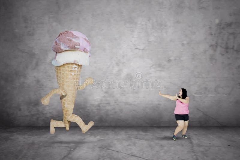 Grosse femme courant à partir d'une crème glacée  images stock