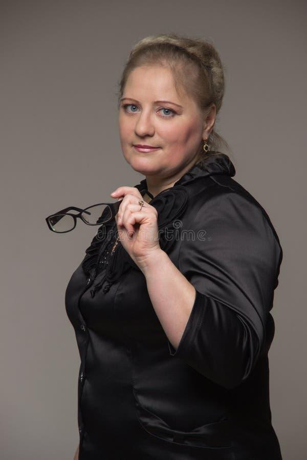 Grosse femme d'affaires dans un costume tenant des verres pour la vision image stock