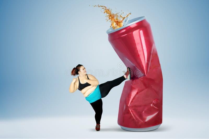 Grosse femme donnant un coup de pied la boisson non alcoolisée image stock