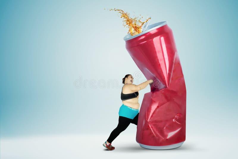 Grosse femme frappant une boisson non alcoolisée photo stock