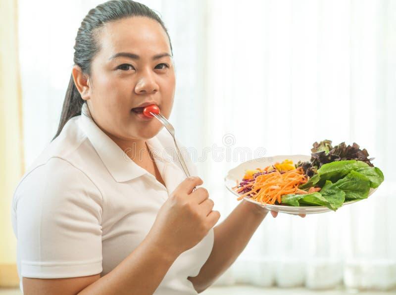 Grosse femme mangeant de la salade image stock