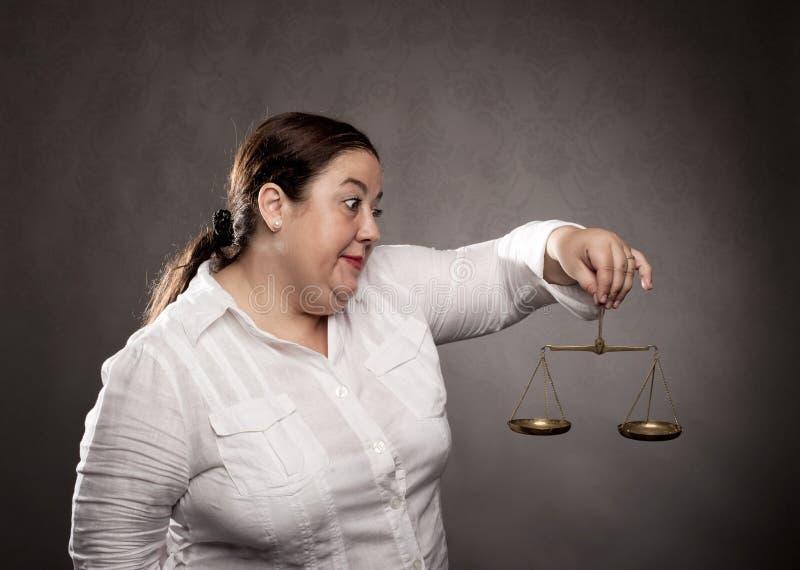 Grosse femme tenant une échelle photo stock