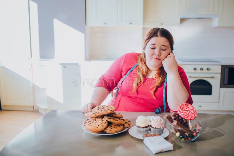 Grosse jeune femme dans la cuisine reposant et mangeant de la nourriture douce Regard modèle ennuyé de taille plus aux crêpes et  photos stock