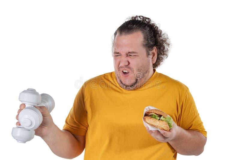 Grosse nourriture malsaine mangeuse d'hommes drôle et essai de prendre l'exercice d'isolement sur le fond blanc image stock