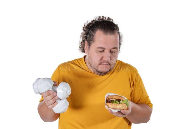 Grosse nourriture malsaine mangeuse d'hommes drôle et essai de prendre l'exercice d'isolement sur le fond blanc photographie stock