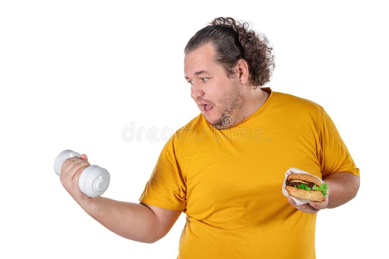 Grosse nourriture malsaine mangeuse d'hommes drôle et essai de prendre l'exercice d'isolement sur le fond blanc photo stock