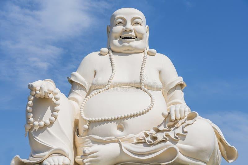 Grosse statue blanche riante de Bouddha avec le fond de ciel bleu photographie stock