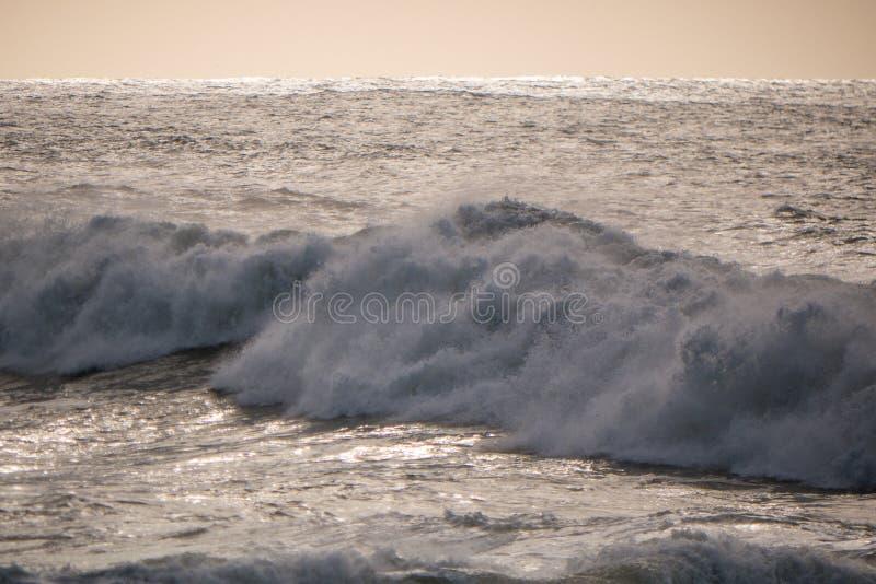 Grosse vague blanche rugueuse se brisant au crépuscule avec une lumière dorée douce images stock