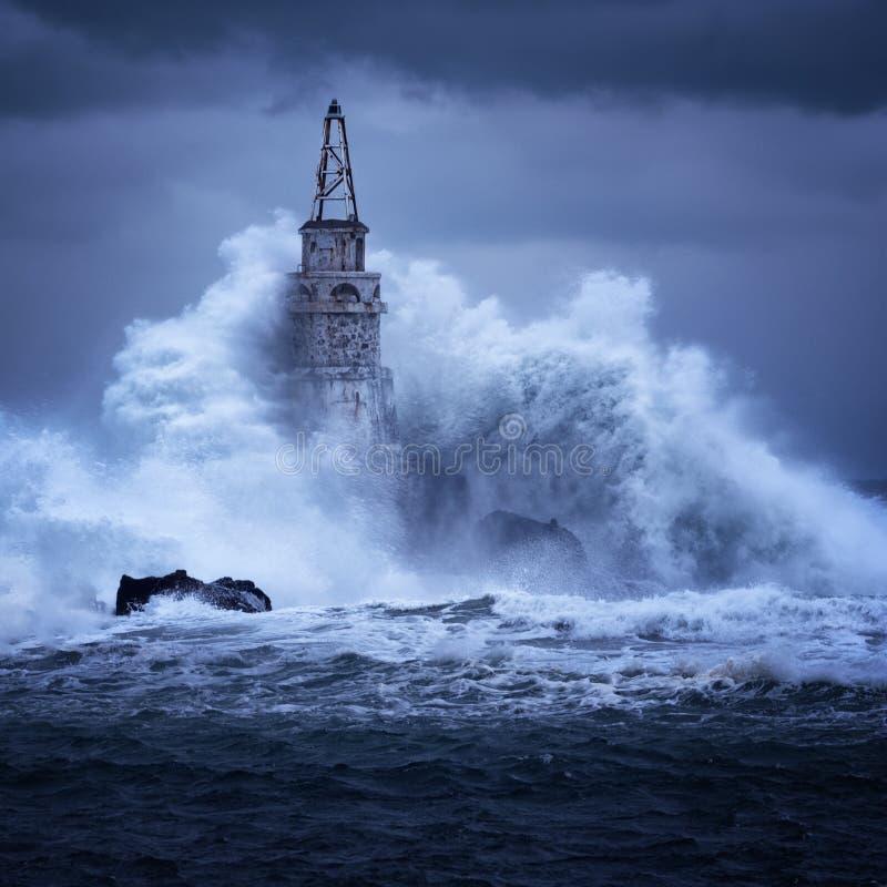 Grosse vague contre le vieux phare dans le port d'Ahtopol, Mer Noire, Bulgarie, un jour de tempête photo stock