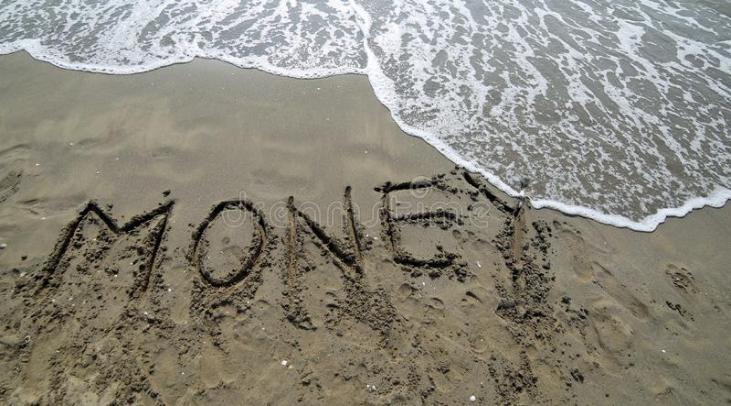 GROSSES Text GELD auf dem Sand des Meeres stockfotografie