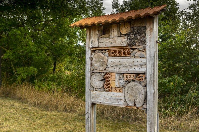 Grosses und schönes Insektenhotel im Flur in der Nähe einer Bucht mit Fliesendach zum Schutz vor Regen lizenzfreie stockbilder