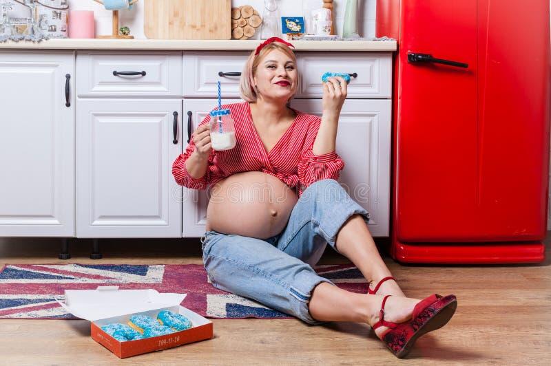 Grossesse et concept malsain de consommation : la femme enceinte mange un beignet savoureux photo stock