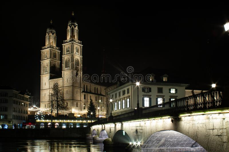 Grossmunster protestant church illuminated at night in Zurich  photographed from across the Limmat river with the old bridge stock images
