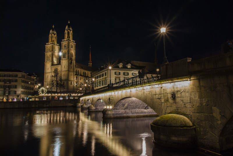 Grossmunsterkerk en Zürich de stad in bij nacht royalty-vrije stock foto's