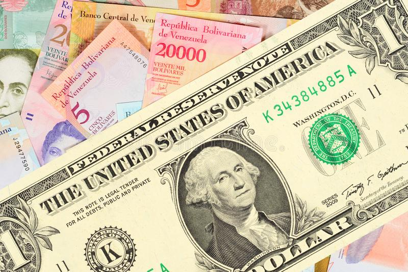 Grote één-dollar rekening tegen de achtergrond van vele kleine Venezolaanse bankbiljetten Het concept hyperinflation in Venezuela stock foto's