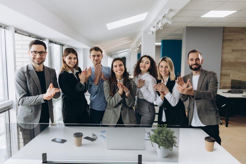 Grote baan! Het succesvolle commerciële team slaat hun indient modern werkstation, vierend de prestaties van nieuw product stock foto's