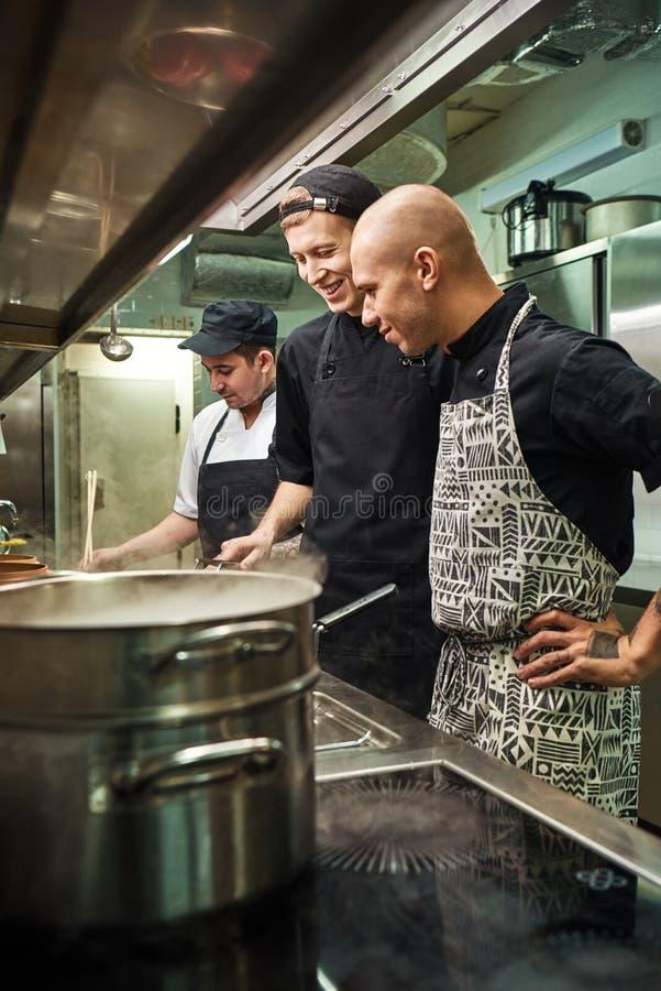 Grote Baan Vrolijke professionele chef-kok die hoe zijn twee medewerkers in een restaurantkeuken koken kijken royalty-vrije stock fotografie