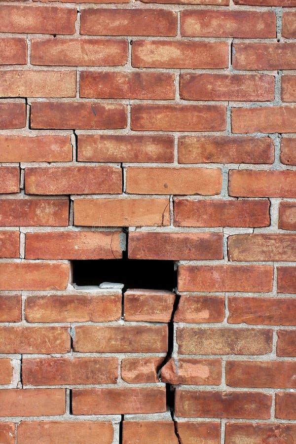 Grote bakstenen muur met behoefte aan reparatie, met barsten door en secties het missen stock fotografie