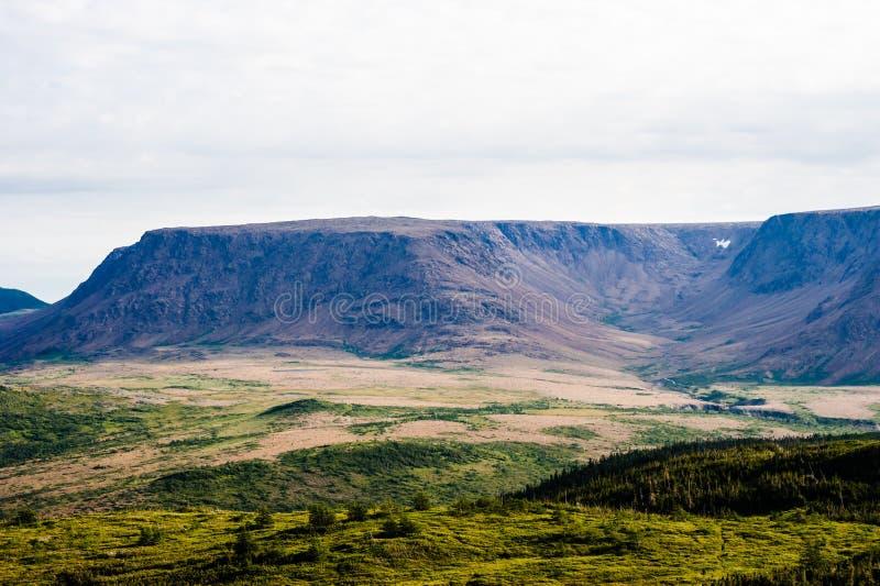 Grote bergplateau en vallei onder bewolkte hemel stock afbeelding