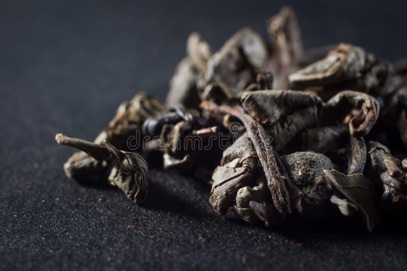 Grote bladeren van droge groene thee in een samengeperste staat op een donkere achtergrond stock foto
