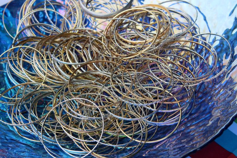 Grote blauwe glaskom die met eenvoudige gouden en zilveren armbandarmbanden wordt gevuld stock afbeelding
