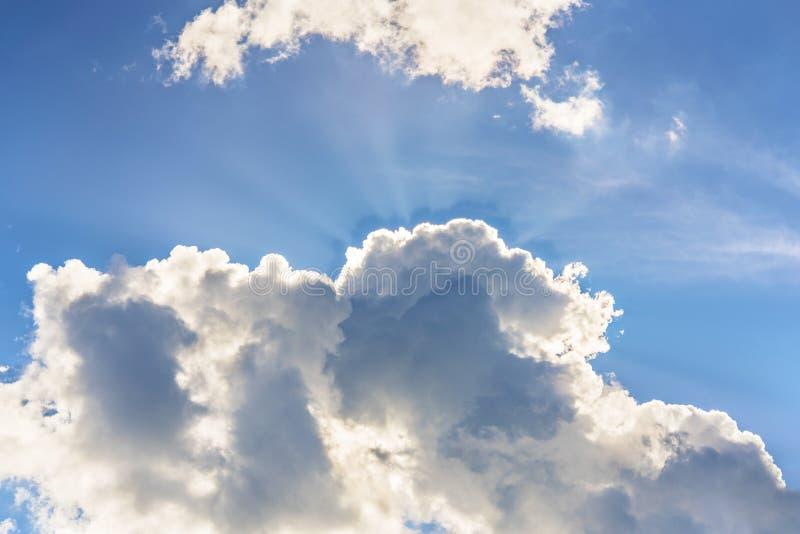 Grote blauwe hemel en grote wolken die door de stralen van de zon wordt doordrongen stock afbeeldingen