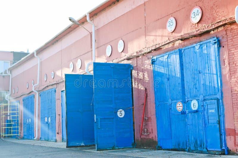 Grote blauwe houten open poorten van hangaars, pakhuizen, garages voor vrachtwagens In een groot rood industrieel baksteengebouw royalty-vrije stock foto