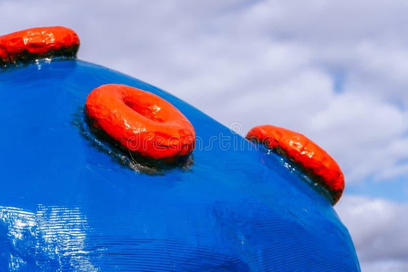 Grote blauwe plastic bal met rode knopen op de achtergrond van wolken royalty-vrije stock foto