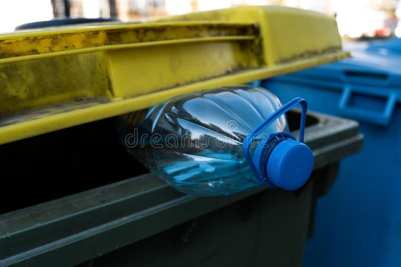 Grote blauwe plastic fles in een geelgroene afvalbak - recycleer voor aard stock afbeeldingen