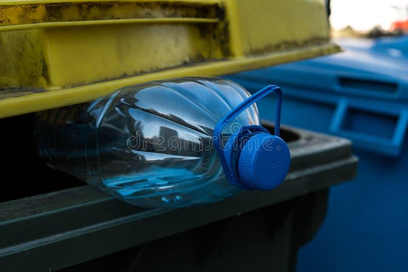 Grote blauwe plastic fles in een geelgroene afvalbak - recycleer voor aard royalty-vrije stock foto